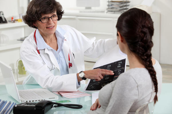 When should a lady get her first gynecologist exam?