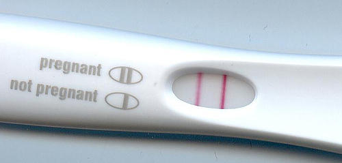 Can ovarian cysts make a woman have a false pregnancy test result?