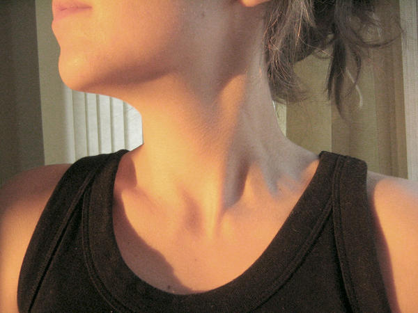 What causes pain and some swelling in the lower right front of my neck?
