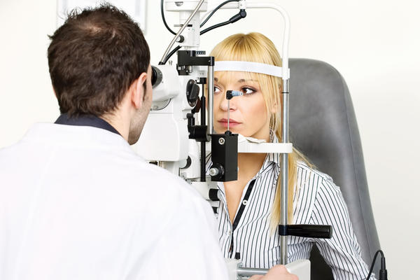 What is an ophthalmologist looking at/for when he puts a lens on the patient's eye after numbing it and looking through a slit lamp?