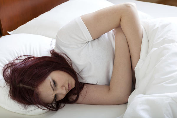 What causes severe nausea during a woman's period?